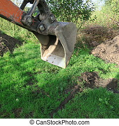 the shovel of a mini digger in the meadow while working in...