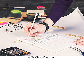 Charts in copybook - Businessman drawing business charts in...