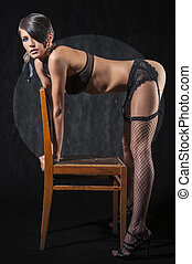 Sensual brunette woman bent over chair, posing in sexy...
