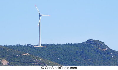 Single wind mill on top of green mountain