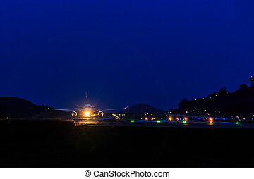 Passenger Airplane at landing strip in the night - Front...