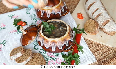 Add salt to the soup in a pot on a Russian holiday table -...