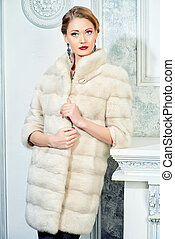mink fur coat - Elegant young woman in evening dress and...
