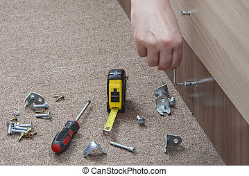 Close-up of carpenter hand tightens fixing screw, using key...