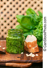 Fresh homemade Basil pesto with pine nuts in a glass jar , sprigs of Basil and toast on the table
