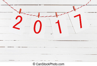 Paper or photo frames with 2017 figures hanging on the red striped rope . New Year design.  On wooden background.