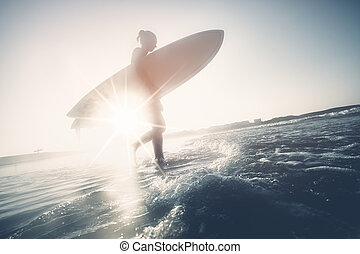 Surfer girl silhouette - Young woman wearing wetsuit,...