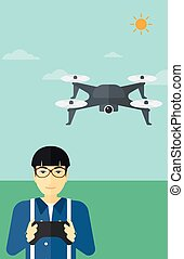 Man flying drone - An asian man flying drone with remote...