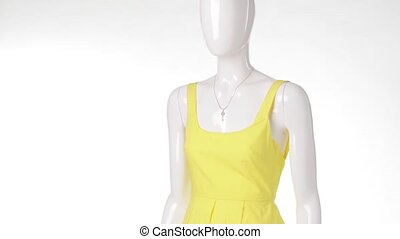 Casual yellow dress on mannequin. Yellow dress with key...