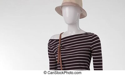 Female mannequin wearing striped top. Striped top with white...