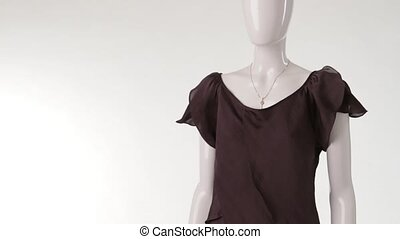 Thin brown blouse on mannequin. Brown blouse with white...