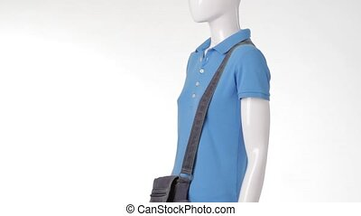 Mannequin in t-shirt turning around. Denim bag and white...