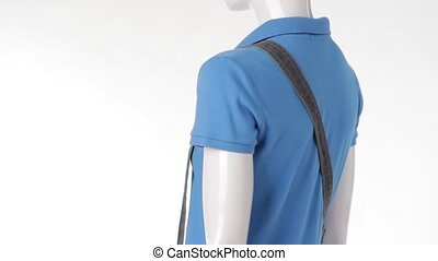 Rotating mannequin in blue t-shirt. Denim strap over...