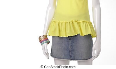 Yellow top in the wind. Colorful bracelets on mannequin's...