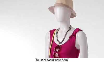 Female mannequin in pink top. Sleeveless top and beige hat....