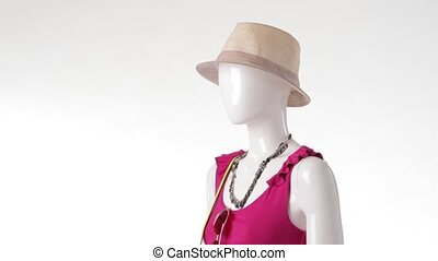 Mannequin in pink top turning Beige headwear and sleeveless...