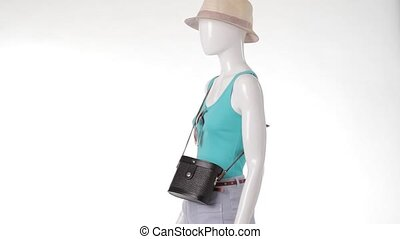 Mannequin in turquoise top turning Beige hat with retro...