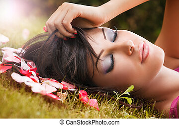 Beauty portrait of woman with flower petals near face
