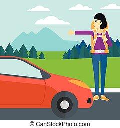Young woman hitchhiking - An asian woman hitchhiking trying...