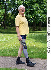 Happy older man walking with prosthetic leg - Single happy...