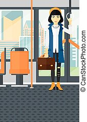 Woman standing inside public transport - An asian woman with...