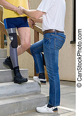 Therapist assisting amputee with leg on stairs -...