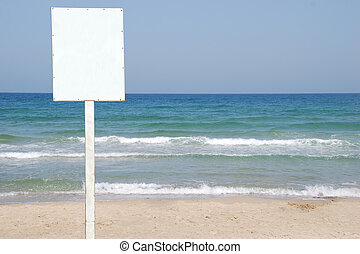 White Sign on the beach - A Blank white Sign on a pole by...
