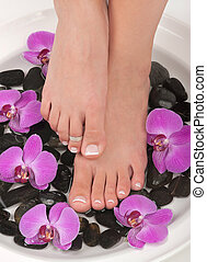 Pedicured feet and orchids