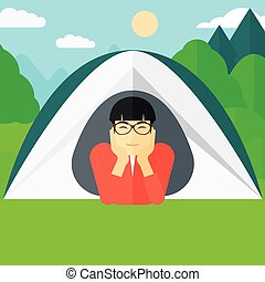 Man lying in tent - An asian man crawling out from a tent on...