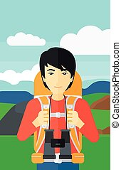 Cheerful backpacker with binoculars. - An asian man with...