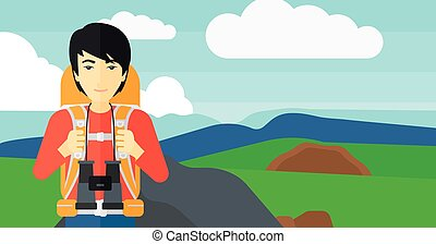 Cheerful backpacker with binoculars - An asian man with...