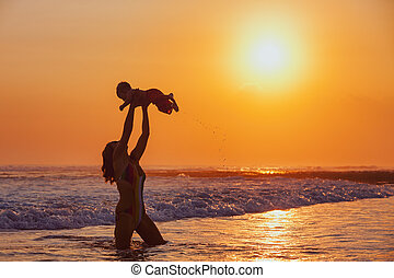 Happy mother tossing up baby son high in sunset sky - Happy...
