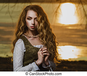Girl with long wavy hair in the sunset.
