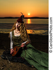 Girl in medieval dress and hat on the lake shore with a...