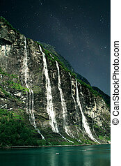 At night, under the light of stars Geiranger fjord, Norway -...