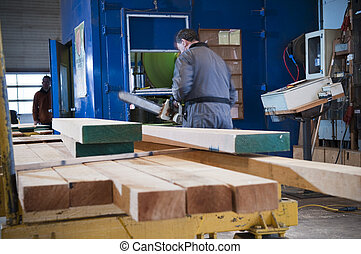 Lumber industry - A man working with processed lumber at a...