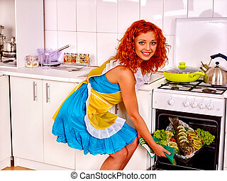 Woman prepare fish with vegetables in oven - Happy woman in...