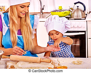 Mother and daughter preparing cookies in the kitchen.
