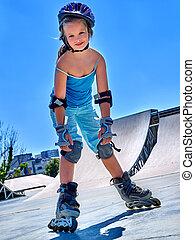 Girl rides on roller skates in skatepark. - Girl riding on...