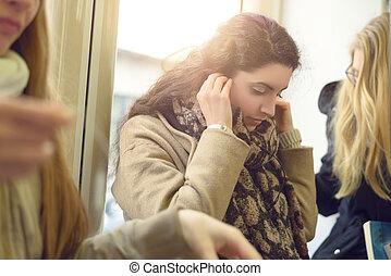 Beautiful young woman placing earphones - Single beautiful...