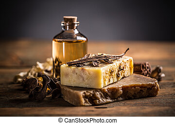 Handmade soap bars with vanilla on wooden background