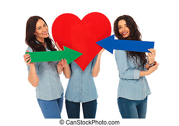 woman covering face with a big heart , friends pointing arrows