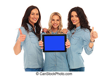 3 women showing the screen of  tablet and make ok