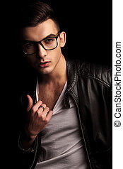 man in black leather and glasses pulling his shirt - closeup...