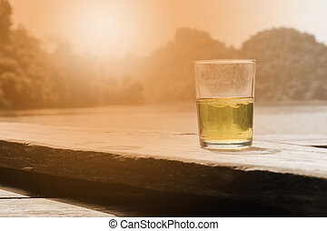 whiskey glass with sunset - whiskey glass on bench with...
