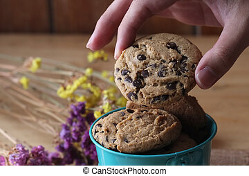 chocolate chip cookie - hand with chocolate chip cookie