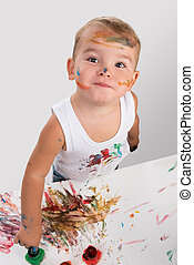 little boy painting with fingers paper in studio