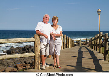 portrait of happy senior couple standing together near beach