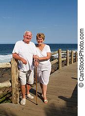 senior couple on holiday posing on wooden beach pathway