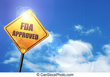 Yellow road sign with a blue sky and white clouds: FDA...